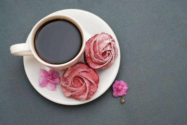 Roze schuimgebak en kopje koffie.