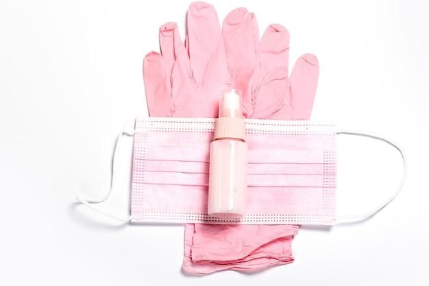 Roze set medische handschoenen gezichtsmasker en ontsmettingsmiddel voor vrouwelijke hygiëne voor gezondheidsbescherming