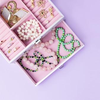 Roze sieradendoosje met kettingen, oorbellen en ringen