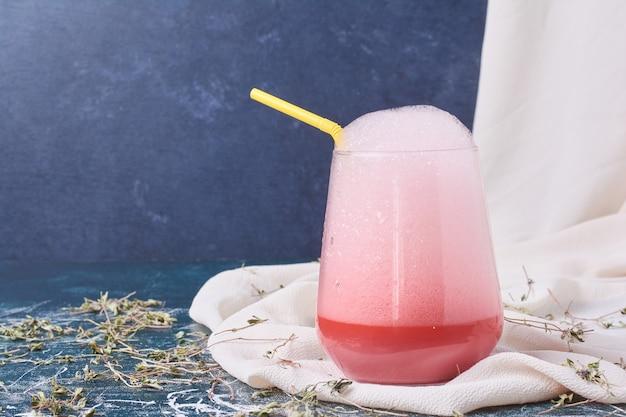 Roze siroop met een kopje drank op blauw.