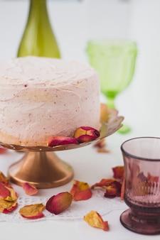 Roze slagroomtaart met bloemen op de feesttafel