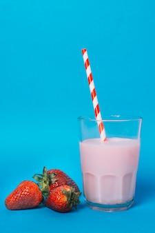 Roze smoothie naast aardbeien met blauwe achtergrond