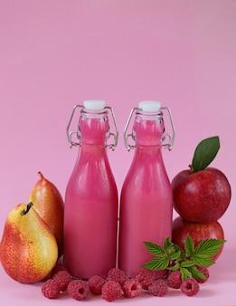 Roze smoothies gemaakt van verse appels, peren en bessen frambozen op roze.