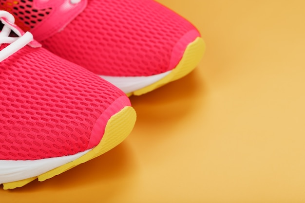 Roze sneakers op een gele achtergrond met vrije ruimte. bovenaanzicht, minimalistisch concept
