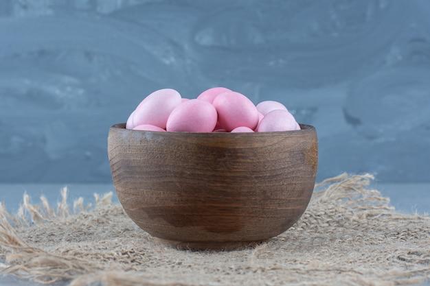 Roze snoepjes in de beker op de onderzetter, op de marmeren tafel.