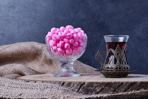 Roze snoepjes in een glazen beker met een glas thee.