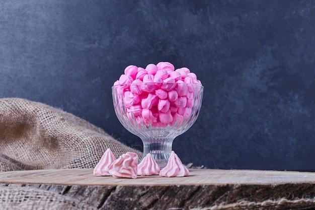 Roze snoepjes in een glazen beker.