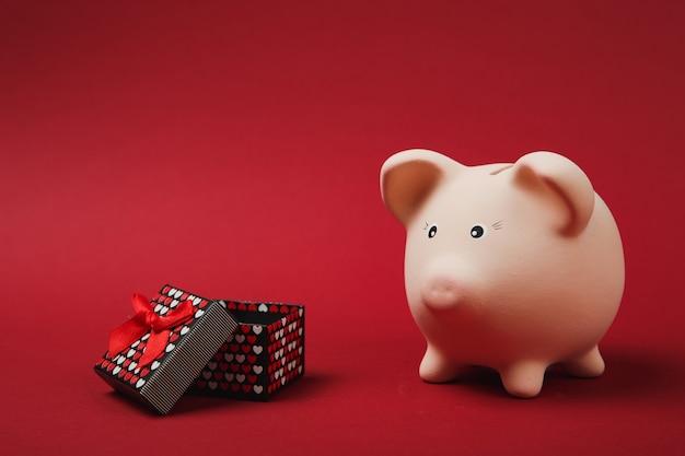 Roze spaarvarken, huidige doos met cadeaulint geïsoleerd op heldere rode achtergrond. geldaccumulatie, investeringen, rijkdomconcept. valentijnsdag vrouwendag verjaardag vakantie. bespotten kopie ruimte.