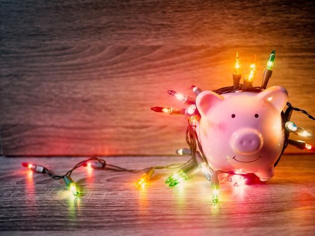 Roze spaarvarken met feestverlichting, geniet van besparingen voor het vakantieconcept.