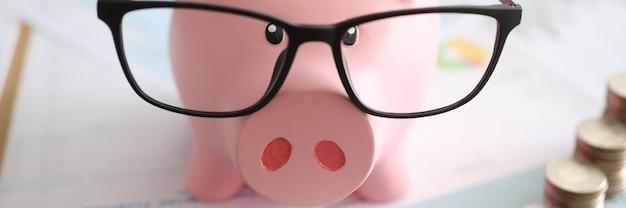 Roze spaarvarken met glazen die zich dichtbij hopen muntstukken en rekenmachineclose-up bevinden. boekhoud- en controleconcept