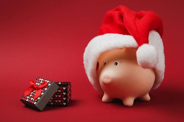 Roze spaarvarken met kerstmuts, huidige doos met cadeau lint geïsoleerd op rode achtergrond. geldaccumulatie, investeringen, rijkdomconcept. gelukkig nieuwjaar, verjaardag vakantie. bespotten kopie ruimte.