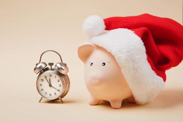 Roze spaarvarken met kerstmuts, wekker geïsoleerd op pastel beige achtergrond. geldaccumulatie, investeringen, bank- of zakelijke diensten, rijkdomconcept. kopieer ruimte reclame mock-up.