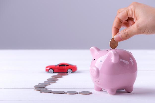 Roze spaarvarken, munten en een auto. vrouwenhand die muntstuk zetten aan spaarvarken.