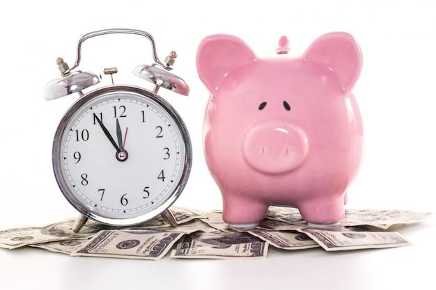 Roze spaarvarken naast wekker op dollars