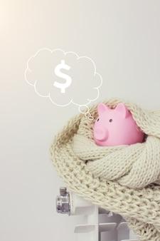 Roze spaarvarken op radiator met digitale hologramdollar in wolkengedachte boven zijn hoofd op blauwe achtergrond. concept van het betalen voor verwarming in huis.