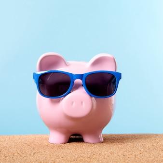 Roze spaarvarken strand reizen vakantie besparingen zonnebril.