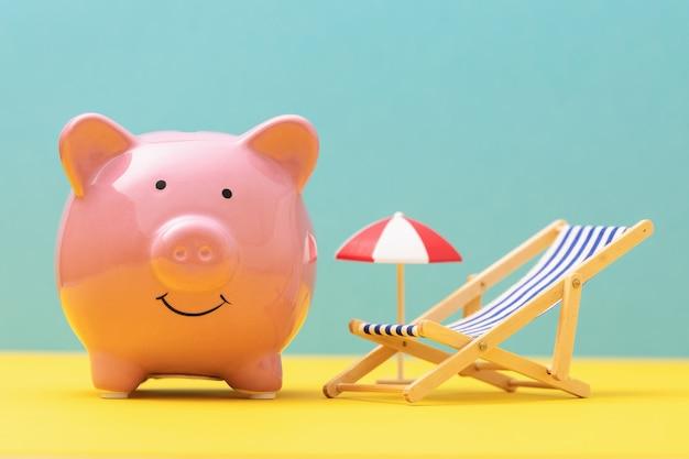 Roze spaarvarkenstuk speelgoed ligstoel en paraplu op gekleurd de besparingsconcept van het achtergrondvakantiegeld