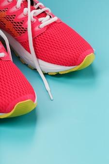 Roze sportschoenen voor hardlopen op een blauwe achtergrond met vrije ruimte. bovenaanzicht, minimalistisch concept