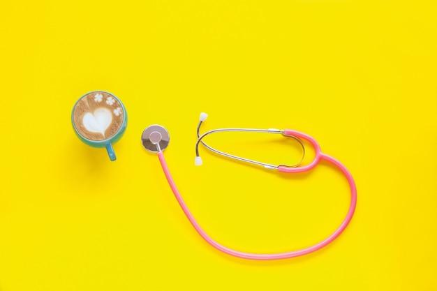 Roze stethoscoop en warme koffie op kleur achtergrond