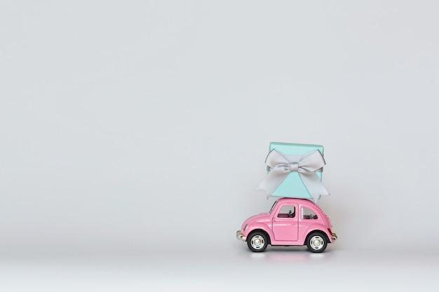 Roze stuk speelgoed auto die giftdoos op dak op wit levert