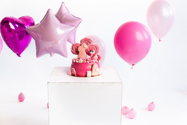 Roze taart voor de verjaardag van een meisje van een jaar ballonnen eenhoorn