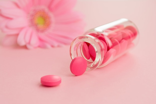 Roze tabletten en glazen fles op een lampje.