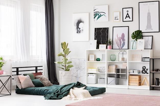 Roze tapijt naast groene matras in helder slaapkamerinterieur met ficus en galerij met posters