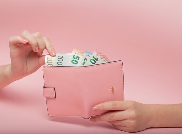 Roze tas en eurobankbiljetten in vrouwelijke handen op roze achtergrond. bedrijfsconcept en instagram