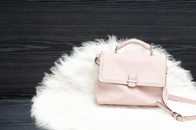 Roze tas op witte vacht, zwarte tafel. modieus concept