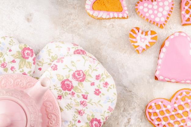 Roze theepot, bloemhandschoenen en plaat van handgemaakte geglazuurde hartvormige koekjes