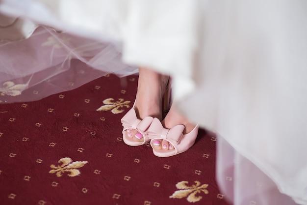 Roze trouwschoenen met strik aan de voeten van de bruid in de witte jurk close-up