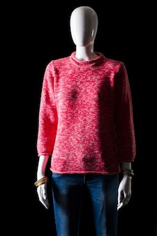 Roze trui met blauwe jeans. jeans en pullover op etalagepop. heldere outfit voor de vrouw voor de lente. warme kleuren en eenvoudig patroon.