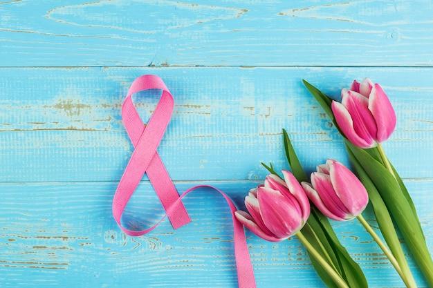 Roze tulp bloem en 8e lint symbool op blauwe houten tafel achtergrond met kopie ruimte voor tekst. liefde, gelijke en internationale vrouwendag concept