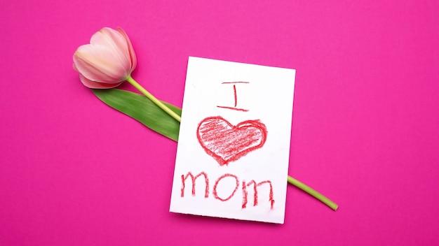 Roze tulp met i love mom kaart erop. roze achtergrond
