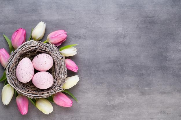 Roze tulp met roze eieren nest op een grijze pasen-wenskaart.