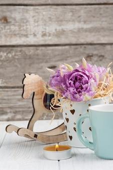 Roze tulpen, blauwe kop, brandende kaars en hobbelpaard