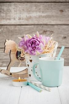 Roze tulpen, blauwe kop, rietjes, brandende kaars en hobbelpaard