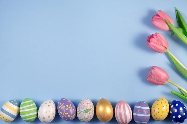 Roze tulpen bloemen en kleurrijke eieren op roze achtergrond. kaart voor vrolijk pasen. wachten op de lente. wenskaart. hallo lente en pasen concept. verse tulpen. platliggend, bovenaanzicht, ruimte kopiëren