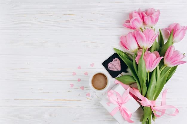 Roze tulpen, cadeau, kopje koffie en papier harten op witte houten achtergrond.