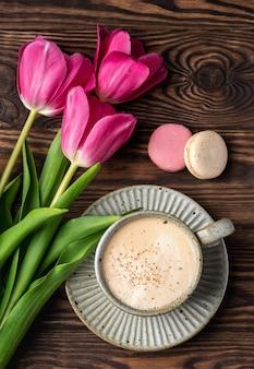 Roze tulpen, cup met koffie en bitterkoekjes op een houten tafel