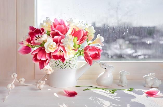 Roze tulpen en witte fresia bloemen met keramiek