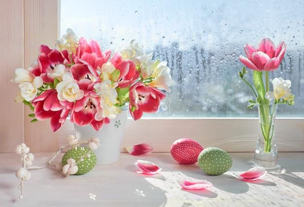 Roze tulpen en witte fresia bloemen met pasen decoraties op het venster bord