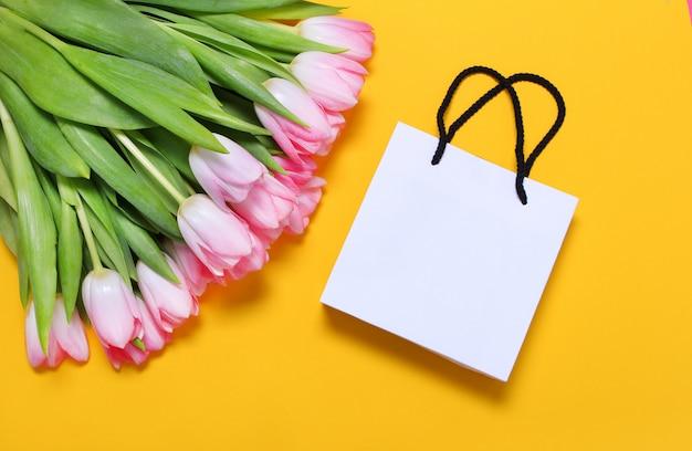 Roze tulpen en witte geschenk tas op gele achtergrond.