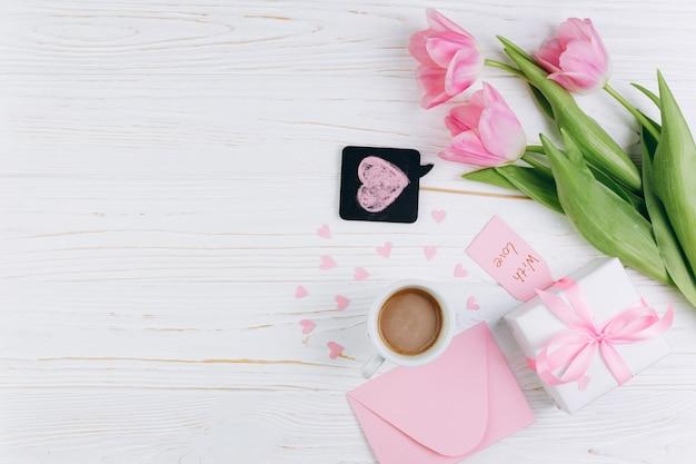 Roze tulpen, envelop, cadeau, kopje koffie en papier harten op witte houten achtergrond