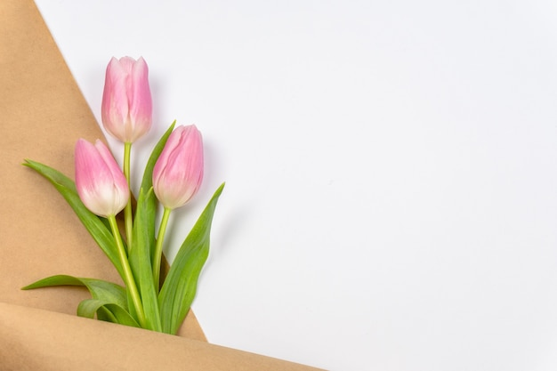 Roze tulpen in ambachtelijk papier op witte achtergrond met kopie ruimte pasen valentijnsdag