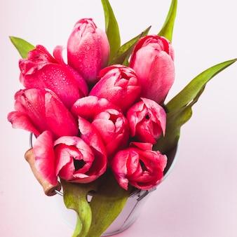 Roze tulpen in decoratieve emmer close-up
