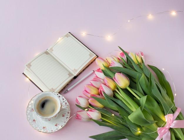 Roze tulpen met een roze tape, een kopje koffie en een notitieboekje met een pen