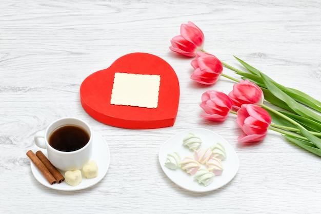Roze tulpen, mok koffie en marshmallow. rode hartvormige geschenkdoos. schone ansichtkaart