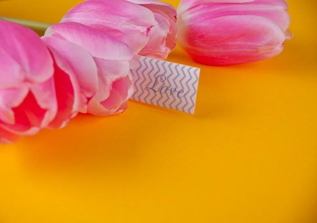 Roze tulpen op de gele achtergrond met de liefdesbrief van de notaliefde