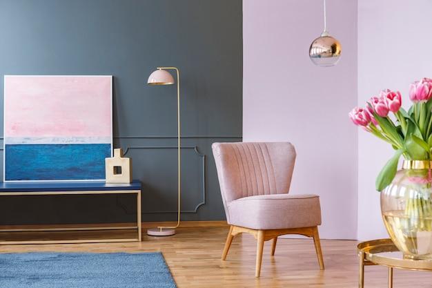 Roze tulpen op tafel in pastel woonkamer interieur met fauteuil en lamp in de buurt van schilderen. echte foto